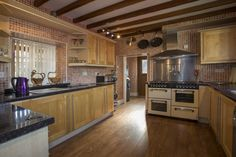 Country style kitchen with wood beamed ceiling, wood floors and wood cabinets.  #kitchen #kitchenremodeling #designideas