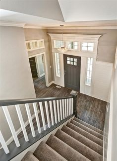 Entryway with gray stair rail and white ballusters. Crystal entry chandelier. Tuftex carpet with Manningtons Restoration Collection laminate flooring in Black Forest Oak fumed. Benjamin Moore Kendal Charcoal front door with White Dove trim. Transom windows above door frames. by bernadine