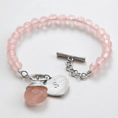 """The ultimate love symbol gets sophisticated in this pink charm bracelet. A string of faceted rose quartz beads—a love symbol in their own right—is finished with a rose-quartz charm, a silver-plated heart pendant and toggle clasp. A stylish and romantic modern piece. Exclusively from RedEnvelope.  6mm faceted rose quartz stones  rose quartz briolette measures 13mm x 13mm  heart charm may be hand-stamped with one letter  silver-plated chain measures 7 1/2""""L"""