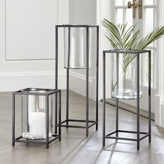 Shop Reflection Framed Vase/Hurricanes.  These contemporary hurricanes elevate candlelight, floating a clear glass vase in an open rectangle of black steel.  Powdercoated frames make them suitable for indoor or outdoor display.