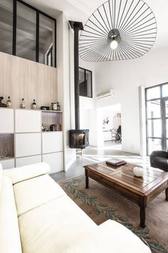 salon moderne gris et bois canapé en cuir noir suspension vertigo