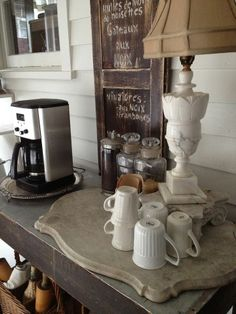 Coffee pot on silver tray, cups & lamp on vintage marble slab.
