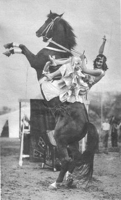 So not actually a rodeo performer but a circus one, still... and note, she's performing this trick sidesaddle and in heels. Take that Roy Rogers!