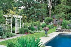 The homeowner of this Connecticut cottage built a fence close to the pool for intimacy, added evergreens for year-round structure, and varied the garden palette with complementary colors.   - CountryLiving.com