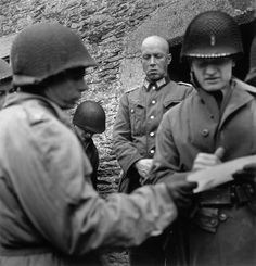 June, 1944. German officer surrendering to American officers.