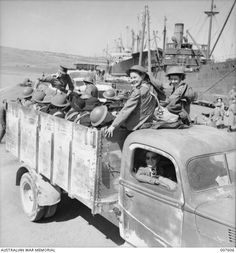 """April 1941 Souda Bay... Crete... Part of an Australian & N.Z. hospital arrive safely in Crete...The worst part of their journey to safety... safely over. Some of these Sisters were wounded in a bombing raid whilst embarking. Identified are: seated on the roof of the truck cab, left to right, Sister O.J """"Jean"""" Bowman and probably Sister Una Mills, both of 2 AGH. The driver is possibly Sister Cook of 2 AGH."""