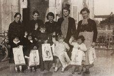 Bambini accompagnati dalle madri davanti alla Casa del Fascio dove hanno ricevuto i doni della Befana Fascista - 1935.