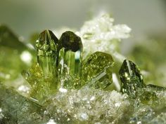 Green crystals. Possibly green quartz (peridot) or green tourmaline- appearing to be hosted on a quartz matrix