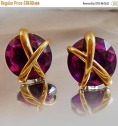 "These #vintage purple rhinestone earrings are so beautiful and sparkly!  They feature large round faceted purple rhinestones with a gold tone ""X"" across them.  The earrings ... #ecochic #etsy #jewelry #jewellery"