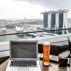 Traveler and entrepreneur Derek @dereklow is working hard to the gorgeous skyline of Singapore with a glass of freshly crafted beer at LeVeL33 #workhardanywhere ---- Use our app to find spaces like these to work from. ----  by: @dereklow
