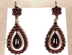 """Victorian Garnet Earrings (c. 1860-1880), The large free swinging drop in the middle is a cabochon garnet with a circular cut out in the backThe teardrop surround and the floral cluster at the top of the ear wire are set with faceted pyrope garnets, often referred to as """"Bohemian"""" garnets. Rose gold setting  The ear wires are lever backs and they are continental in origin."""