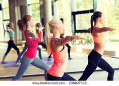 fitness, sport, training and lifestyle concept - group of smiling women stretching in gym - stock photo