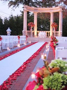 I like the white aisle runner with the pink petals on the side and candles by the chairs.: