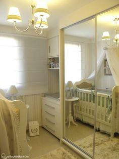 Quarto de bebê com guarda roupas com portas de espelho e lustre.