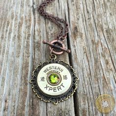 """Beautiful scalloped bronze finish pendant mounted with an antique """"Western Xpert"""" brass 16 gauge shotgun shell with your choice of Swarovski crystal or spent primer. Chain comes in a copper oxidized finish, measures 17 inches and has a front copper toggle closure. Pendant measures 1 1/4 inches in diameter. Shotgun Shell Crafts, Shotgun Shell Jewelry, Ammo Jewelry, Jewelry Necklaces, Shotgun Shells, Jewlery, Make Your Own Jewelry, Jewelry Making, Bullet Necklace"""