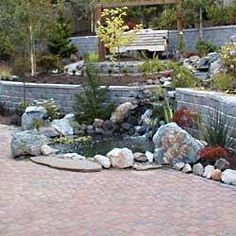 A small pond and waterfall draws the eye from a long retaining wall.  By Blue Valley Aquatic Landscapes | 300 sigalet road Lumby BC v0e 2g6 | 250-547-2525   #vernon #kelowna #rockwork #patio #outdoor www.bluevalley.ca
