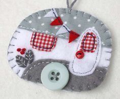Vintage caravan trailer ornament, handmade from felt and decorated with fabric scraps. With tiny felt bunting and buttons for the wheel and door knob.Colors are
