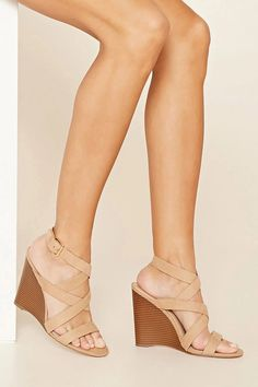 A pair of faux suede sandals with a wedge heel, a buckled slingback strap, and a strappy crisscross design. #stepitup