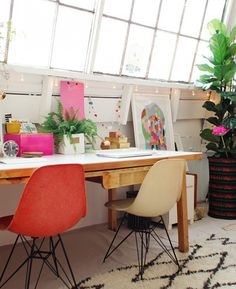 Eclectic home office design featuring a vintage wood table as a desk, orange and butter yellow Eames chairs, colorful artwork, and a fig tree - Workspace Decor & Design Ideas