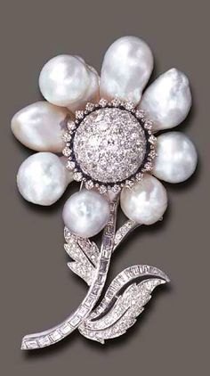 A BAROQUE CULTURED PEARL, DIAMOND AND SAPPHIRE BROOCH Designed as a baroque cultured pearl flower, centering upon a circular-cut diamond bombé pistil, within a circular-cut sapphire and diamond surround, extending circular and baguette-cut diamond stem and leaves, mounted in platinum