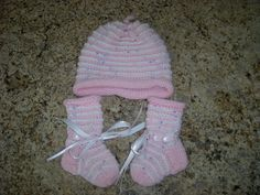 Easy to knit, this set of cap and booties will keep a precious newborn warm. Simple knit and purl stitches create the raised ridges. Knit in the round with an I-cord topper. Knitted Booties, Baby Booties, Knitted Hats, I Cord, Purl Stitch, Baby Hats Knitting, Knit In The Round, Knitting Videos, Cute Hats