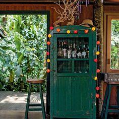 O armário verde, da extinta loja de decoração Jacaré do Brasil, faz as vezes de bar no living. Em cima do móvel, árvore garimpada durante viagem à Califórnia. (Foto: Deco Cury)