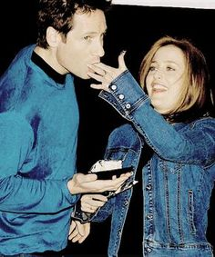 David Duchovny is sucking frosting off of Gillian Anderson's fingers at The X-Files 200th episode celebration. This is what normal people do at their wedding reception.