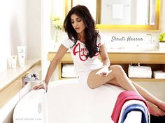 #ShrutiHaasan in a perfect white top and a white casual shorts sitting beside a #bathtub posing #seductively flaunting her toned legs and #thighs.