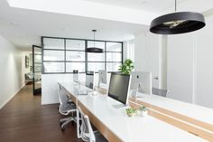 """""""We used understated and refined materials, like oak wood, white lacquered desks, and matte black hardware, for the majority of the space,"""" says the designer. """"Then, we chose impactful materials that made a strong statement, like the black and white cement tiles for the kitchen backsplash and the glass-and-steel doors for the meeting rooms. With a fast-growing business, the needs can change quickly, so designing with flexibility in mind is important."""""""