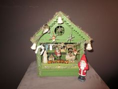 German wooden Christmas stall, ca. 1920.    Size: 26.5 x 25.5 x 33 cm (WxDxH).   With many miniature figurines, Christmas decorations, with small, hand-painted artworks and antique Oblates.  A hand-painted Santa Claus stands in front of the stall.