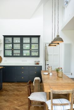 We love this long refectory table with an assortment of old school chairs and benches in the charming arts and crafts kitchen  by deVOL