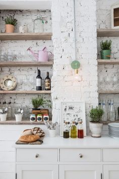 Open wood shelves on white brick wall.