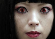A woman puts on red contact lenses at a Halloween event in Kawasaki, near Tokyo.  (Photo by Itsuo Inouye / AP). First published in the October 28, 2012, 1:02 p.m. edition (http://dailysource.org/pictures/show/42123).