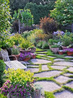 Bench set among flagstones and clusters of container plants.