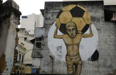 Weight of the world: A young boy sheds a tear as he carries an enormous football on his back - a potent critique of the cost of the tournament / World-Cup-2014-Stunning-photos-reveal-amazing-street-art-streets-Rio-Sao-Paulo-Brazil