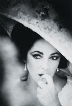 elizabeth taylor @ Black backdrop  -pearl hanging earrings and BIG flowery hat…