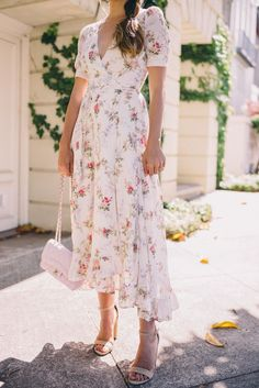 Vestido fluido de flores versatil para una boda y con accesorios mas casual como una sandalia plana y un canasto de rafia para una noche de verano.