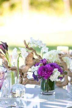 centerpiece idea - grapewood branches, small arrangements with mixed florals and bud vases with single stems