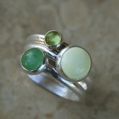 Three sterling silver bands set with gemstones. Chartreuse peridot, grass green aventurine, and lemon chrysoprase cabochons.