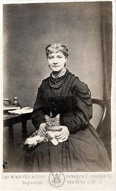 I adore the fact that this woman (identified as Nelly Moore) opted to include her beloved cat in this studio portrait.