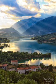 Rays of light filter through the clouds and create beautiful reflections on the lake of Barrea, in the Abruzzo National Park, Italy
