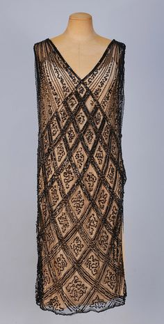 BEADED NET FLAPPER DRESS, 1920's. Sleeveless black cotton net with black bugle beads, sequins and paillettes in a diamond lattice pattern, V-neck and back and one side slit to hip. B-42, L-43. SM. (Lacking under-dress, minor bead losses) excellent. $390.