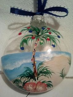 Beach themed christmas ornament with water, sand, palm tree decorated with ornaments. Each one is individual.