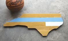 Chapel Hill, Durham, Tobacco Road, The Rivalry. The State of North Carolina is where basketball was perfected. This wall art is made from reclaimed American basketball courts and hand-painted to reflect the colors of the oldest public university in America located in Chapel Hill.  This piece can also be customized with the colors of their in-state rivals just down the road in Durham and Raleigh. Painted, sanded, varnished and ready to hang in the home of any Tar Heel fan.  DETAILS: • Made in…