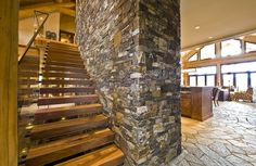 wood stairs against stone wall with glass