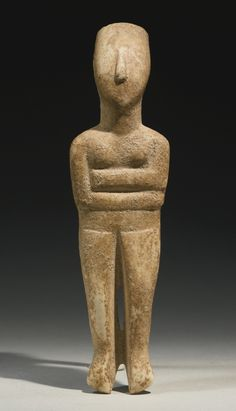 A CYCLADIC FIGURE OF A GODDESS, EARLY BRONZE AGE II, CIRCA 2600-2400 B.C. lying with her arms folded beneath the breasts, with grooved spinal column and V-neck in back, the convex facial plane with pointed chin, small triangular nose, and high forehead. Height 7 1/16 in. 18 cm.