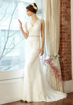Delicate alencon lace appliques drape over soft net on this slip dress to create a charming trumpet style. The neckline is sculpted into a V-neck and plunges into a deep-V back. The thin hand detailed sash cinches the waist.