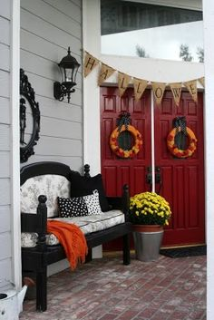 "Cute front porch. I love that the bench is ""universal"" and can be incorporated into all holiday decorations. The banner above the door is cute."