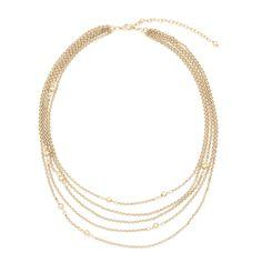 El collar Hamida mide 45 cm y cuenta con 5 cadenas a distintos niveles donde se encuentran pequeños elementos esféricos con 4 baños de oro de 18 kilates.