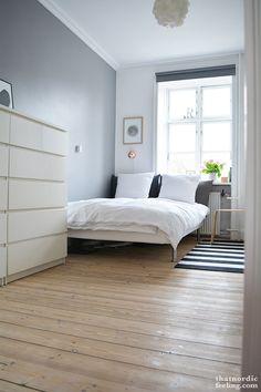 hellgrau/weißes Schlafzimmer mit Bett am Fenster